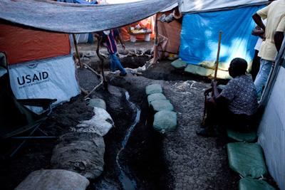 Makeshift tent walls include tarps provided by USAID.