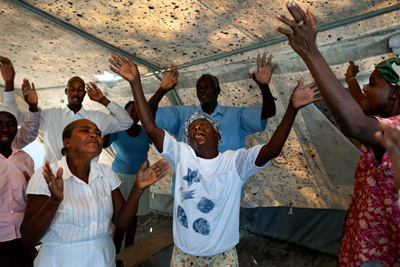 A service in a makeshift church found in the 55,000-person tent camp on the grounds of the Petionville golf club.