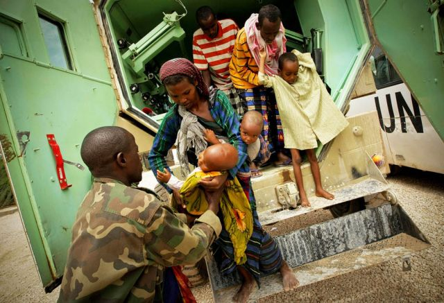 A Somali woman in Mogadishu hands her severely malnourished child to a medical officer of the African Union Mission in Somalia.: Stuart Price/UN/Flickr