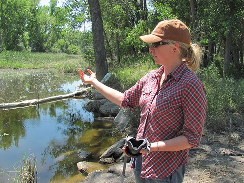 Alexis Bonogofsky points to a pool of oily water left behind on their farm.
