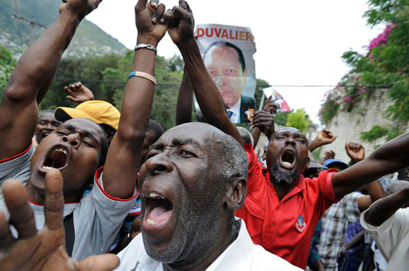 Duvalier supporters react as police take him from his hotel to the courthouse.