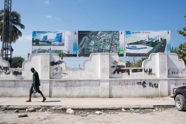 A Haitian walks past government plans for reconstruction at ruined Fort National, Port-au-Prince