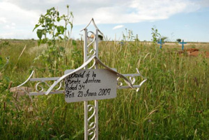 David de la Fuente's humble, hand-painted grave marker is adorned with a simple iron cross.