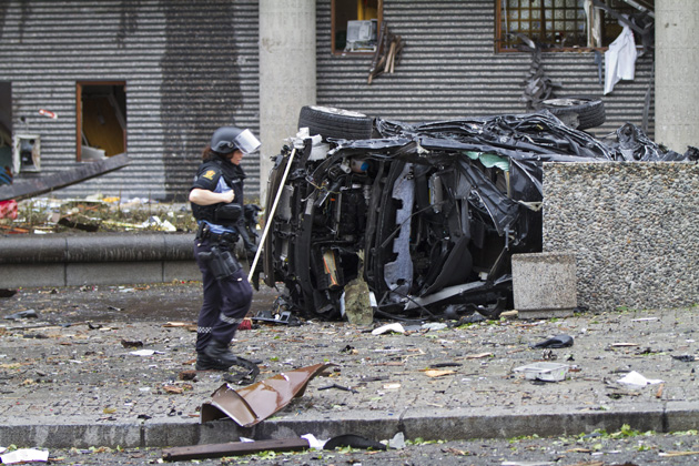 OSLO, NORWAY - Rescue personnel walks among debris, including a heavily damaged vehicle, after an explosion near government buildings in Oslo Friday.: Scanpix/Zuma