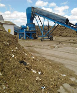 A Recology compost pile containing plastic and other debris