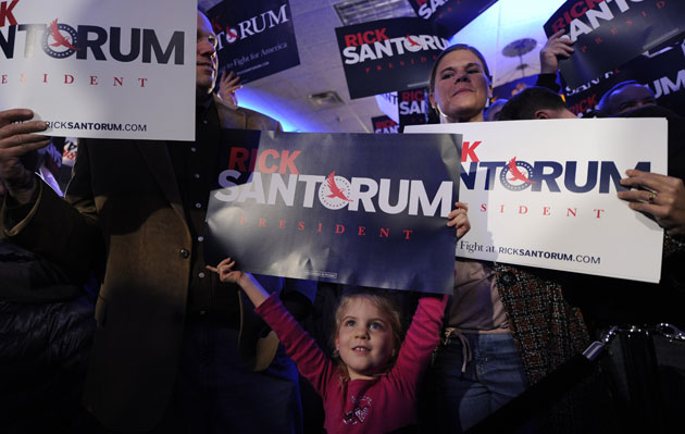holds up a placard during a caucus night event of U.S. Republican presidential candidate, former Pennsylvania Senator Rick Santorum, in Johnston near Des Moines, capital of Iowa, the United States, Jan. 3, 2012.: Zhang Jun/Xinhua/Zuma