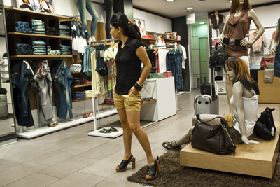 22-year old Monica Joshi tries on a pair of shoes while shopping on her day off in New Delhi, India. Monica Joshi works for a call centre in Gurgaon, suburbs of New Delhi, India.