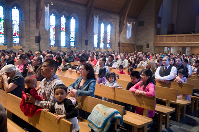 Austin is home to an influx of migrants, seen worhipping at Queen of Angels Church.