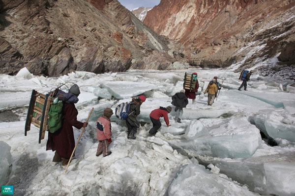Children and parents travel down a Himalayan ice river, Zankar, India.