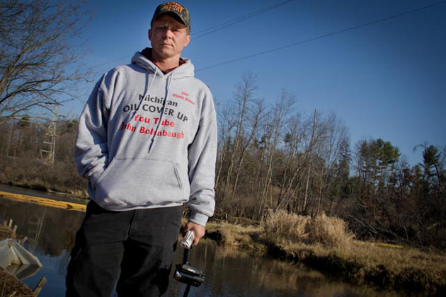 John Bolenbaugh, video camera in hand, stands near the spot on the Kalamazoo River where he says he was ordered to cover over tar sands crude with grass clippings to conceal it from EPA inspectors. His lawsuit, alleging that he was fired by an Enbridge co: Mary Anne Andrei