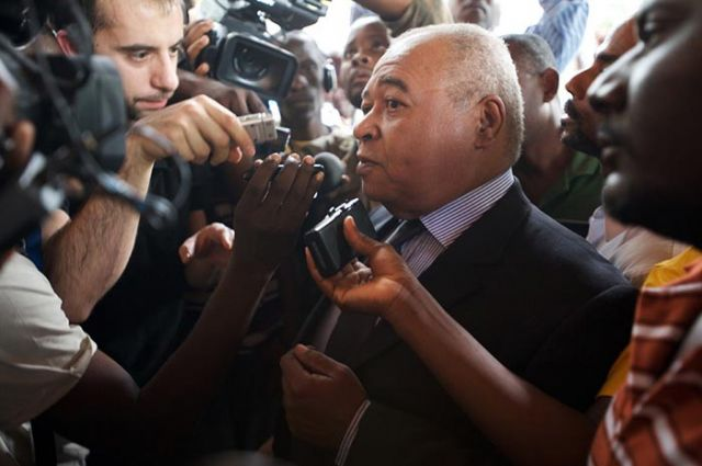 Jean Claude Duvalier's lawyer, Gervais Charles, speaks to press outside the Karibe Hotel. A lot of pushing to get a really simple shot.