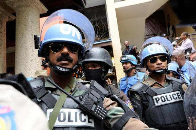 UN police push back against the crush of journalists.