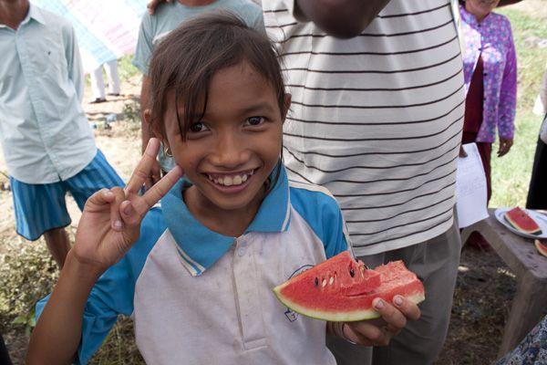 The Nguyens' daughter, Oanh, shows off a melon.: Photo by Kate Sheppard