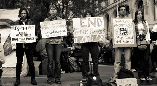 Protesters hold signs in Zuccotti Park.: VBlessNYC/Flickr