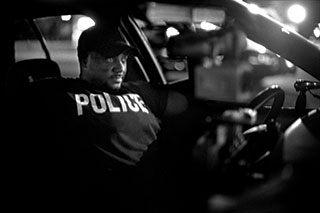 A wary Detroit police officer keeps watch over an unruly crowd after an arrest on the East Side.
