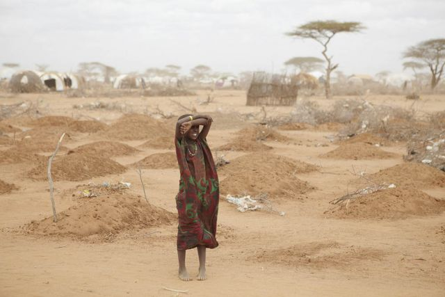 On the edge of the Dadaab refugee camp, a young girl stands amid the freshly made graves of 70 children, many of whom died of malnutrition.: Andy Hall/Oxfam/Flickr
