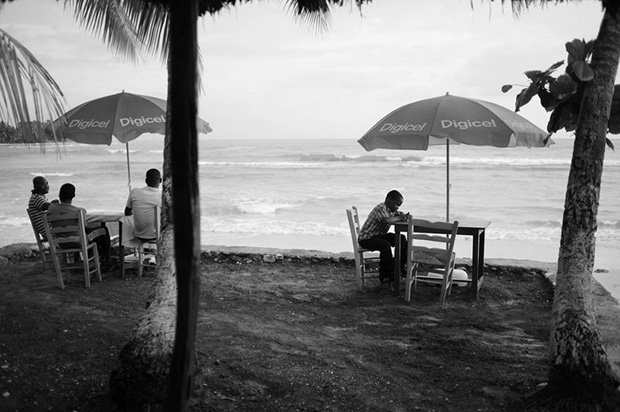 A boy reads a book at one of the tables at La Reference, a restaurant and bar in Jacmel.