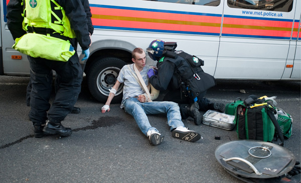 Paramedics tend to a young man injured in the riots.: National News/ZUMA