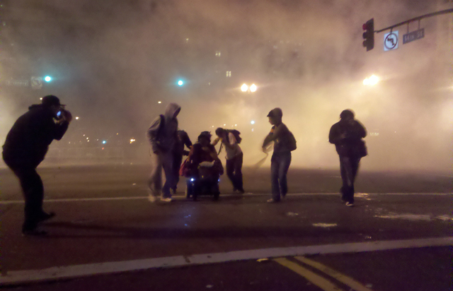 A woman in a wheelchair is tear-gassed as police disperse protesters at Occupy Oakland.: @Adreadonymous/Twitter