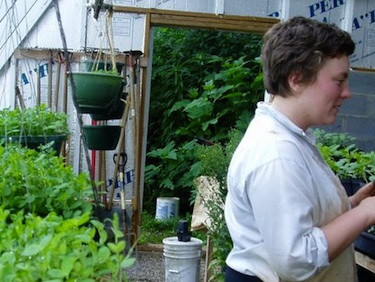 Rebecca Bilodeau, a 2011 farm hand, tends plants in the passive-solar greenhouse.